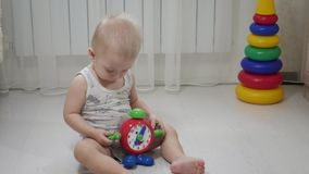 Poco bebé que juega con los pequeños bloques coloridos de un constructor en el cuarto en el piso Niño que juega con coloreado almacen de video