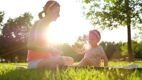 Poco bebé que se sienta con su madre en hierba verde en verano metrajes