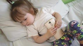 Poco bebé se cayó el jugar dormido en teléfono en la instalación médica en cama de hospital Restauración del niño en sala de hosp metrajes