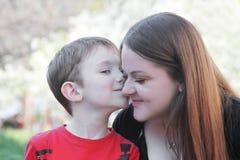 Poco brothet que besa a la hermana en mejilla Foto de archivo libre de regalías
