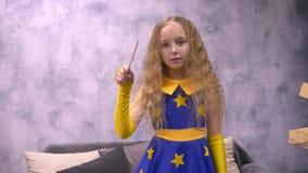 Poco bruja que mueve la vara mágica durante el encanto en Halloween, fondo del copyspase almacen de video