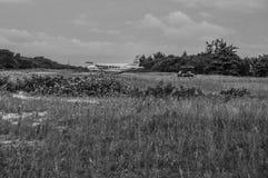 Poco campo de aviación con Cessna y el carro en una isla caribeña, calafate de Caye, Belice del oro fotografía de archivo libre de regalías