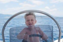 Poco capitano divertendosi sulla barca nel mare fotografia stock libera da diritti