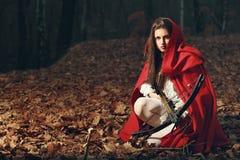 Poco cappuccio di guida rosso nella foresta scura Immagini Stock