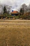 Poco casa por la orilla del lago dejado-hacia fuera imagenes de archivo