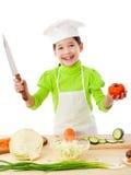 Poco cocina con el cuchillo y los tomates Imagenes de archivo
