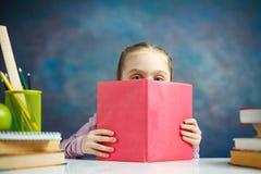 Poco colegiala primaria leyó el retrato del estudio del libro foto de archivo libre de regalías