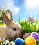 Arte poco conejito de pascua y huevos de Pascua en hierba verde Fotografía de archivo