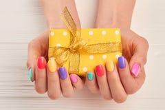 Poco contenitore di regalo in mani manicured femmina immagini stock