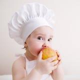 Poco cuoco mangia una mela Fotografia Stock Libera da Diritti