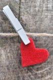 Poco cuore rosso che appende su una corda Fotografia Stock