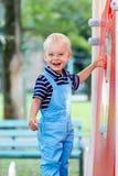 Poco, dos años el jugar sonriente del muchacho en el patio Fotografía de archivo