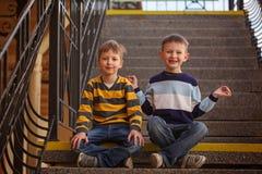 Poco dos muchachos que se sientan en la escalera en día soleado fotos de archivo libres de regalías