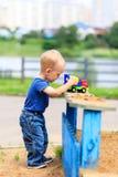 Poco, due anni di gioco sorridente del ragazzo nella sabbiera facendo uso di un escavatore Immagini Stock Libere da Diritti