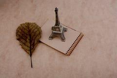 Poco Eiffel Tower modelo, cuaderno y una hoja seca Foto de archivo libre de regalías
