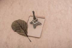 Poco Eiffel Tower modelo, cuaderno y una hoja seca Foto de archivo