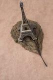 Poco Eiffel Tower modelo y una hoja seca Fotografía de archivo libre de regalías