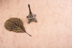 Poco Eiffel Tower modelo y una hoja seca Foto de archivo