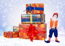 Poco elfo di natale con i grandi contenitori di regalo Immagine Stock