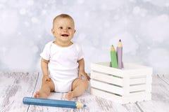 Poco fare da baby-sitter sul pavimento con le grandi matite Immagini Stock Libere da Diritti
