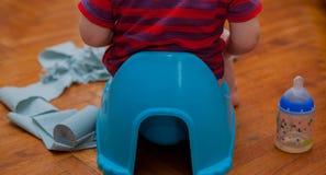 Poco fare da baby-sitter sul vaso da notte con la carta igienica e sulla tettarella su un fondo marrone fotografia stock libera da diritti
