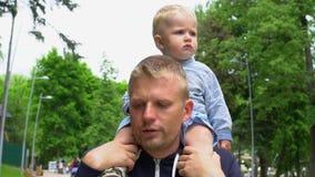 Poco fare da baby-sitter sveglio sul suo collo del ` s del padre nel giorno del ` s del padre del parco video d archivio