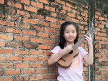 Poco gioco da bambini asiatico il melodion, vecchio muro di mattoni immagini stock libere da diritti