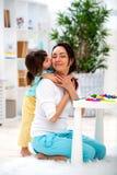 Poco hija abraza y besa a la mamá Familia feliz y amor Día del `s de la madre fotografía de archivo libre de regalías