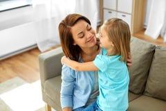 Poco hija que abraza a su madre en casa imagen de archivo
