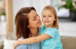 Poco hija que abraza a su madre en el sof? en casa imagen de archivo
