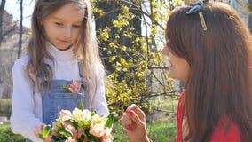 Poco hija rubia toma una flor del ramo y la pone en un bolsillo de su dril de algodón total ` Feliz s de la madre almacen de metraje de vídeo