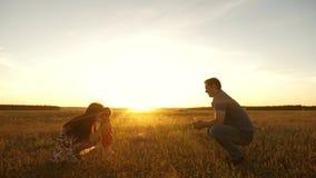 Poco hija va de pap? a la mam? en el sol Familia joven feliz con el ni?o que camina en campo del verano Madre sana almacen de video