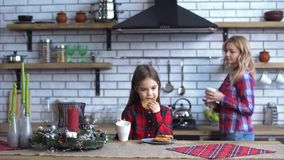 Poco hija y madre joven hermosa en las camisas a cuadros que desayunan en la cocina junto La muchacha come metrajes