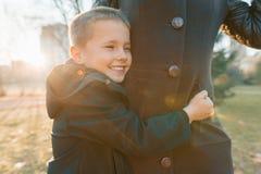 Poco hijo que abraza a su madre, muchacho que sonríe, día soleado en el parque, hora de oro imagenes de archivo