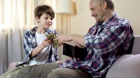 Poco hijo que pide que el padre dé más dinero suelto, necesidades financieras, paternidad foto de archivo