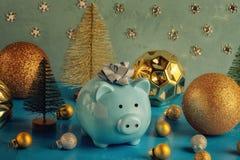 Poco hucha azul con un arco en su cabeza Cerca están los pequeños árboles de navidad decorativos y muchas bolas de oro de fotos de archivo