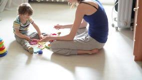 Poco juegos del beb? en el piso blanco con la mam? metrajes
