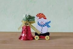 Poco juguete temático de la Navidad con el muñeco de nieve, el oso de peluche, la bola y las campanas rojas imagen de archivo