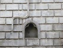 Poco lugar en una pared de piedra pintada blanca del ladrillo con el alambre de la electricidad foto de archivo