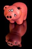Poco maiale del giocattolo su una tavola riflettente Immagini Stock