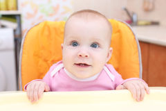 Poco 7 mesi di neonata sulla sedia del bambino in cucina Fotografia Stock