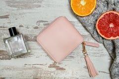 Poco monedero, perfume y fruta cítrica femeninos rosados en un backgro de madera Fotografía de archivo