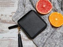 Poco monedero, suéter y fruta cítrica para mujer negros en un fondo de madera Concepto de la manera Imágenes de archivo libres de regalías