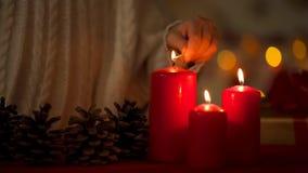 Poco muchacha adorable que enciende velas el la Nochebuena, creencia en futuro feliz imagen de archivo