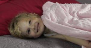 Poco muchacha alegre oculta debajo de una manta en cama en casa Bastante, niña almacen de metraje de vídeo