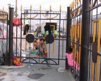 Poco muchacha de calle marrón mira hacia fuera a través de las barras de la cerca imagen de archivo libre de regalías