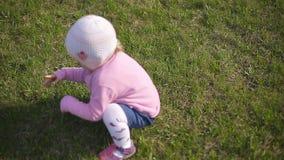 Poco muchacha de dos años en un casquillo hecho punto que juega en hierba verde almacen de metraje de vídeo
