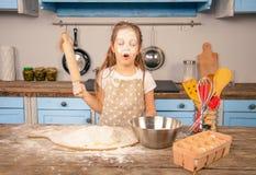 Poco muchacha de la hija del niño está ayudando a su madre en la cocina a hacer la panadería, galletas Ella tiene una inundaci imagenes de archivo