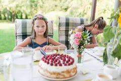 Poco muchacha de risa en su fiesta de cumpleaños en la terraza del jardín que se sienta en la tabla con una torta de cumpleaño imagen de archivo libre de regalías