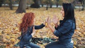 Poco muchacha del pelirrojo con su mamá pasa tiempo en parque del otoño Juegan y aplauden las manos almacen de video